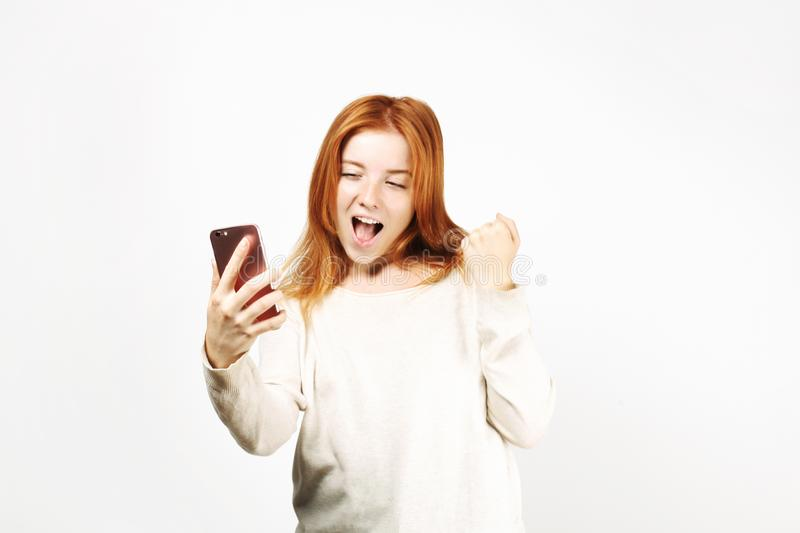 Beautiful red headed young woman posing, showing emotional facial expressions and making funny faces with mobile phone. Lucky beautiful young happy woman with royalty free stock photo