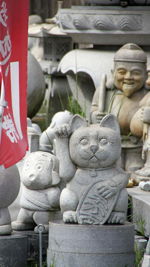 Lucky cat and other stone statues in Japan. Japanese Maneki-neko or beckoning cat and other stone statues royalty free stock image