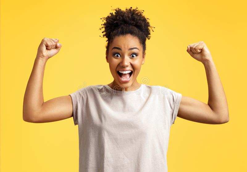Lucky girl winner clenches fists. Photo of african american girl royalty free stock photography