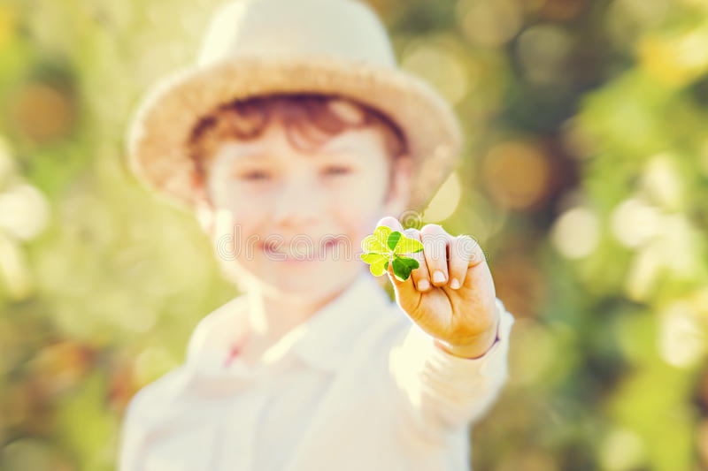 Lucky happy boy in hat holds four leaf clover stock image