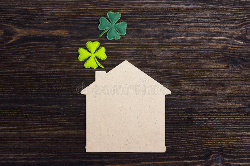 Lucky home symbol with four-leaf clover on wooden background. Co royalty free stock photo