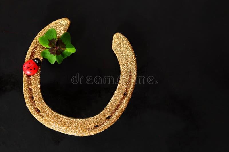 Lucky horseshoe with shamrock and ladybug royalty free stock photo