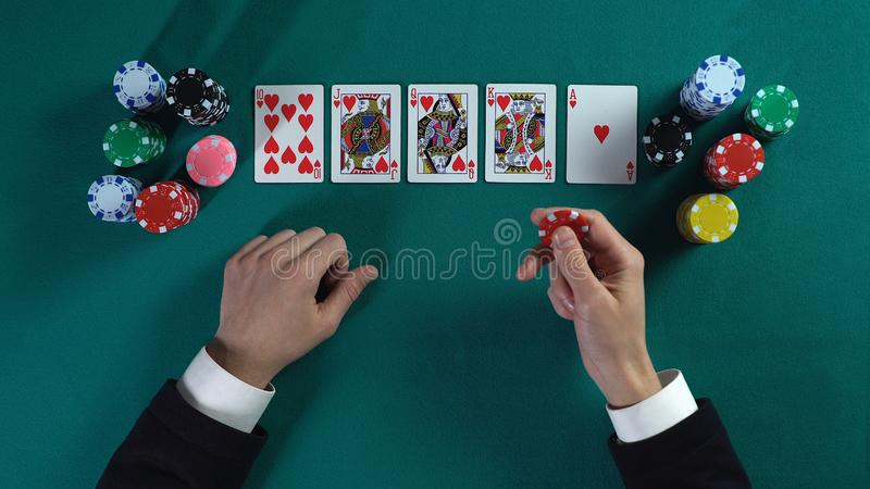 Lucky man has royal flush hand, wins much money in poker game, enjoying success stock photos