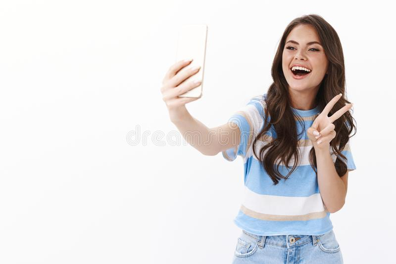 Lucky optimistic cute modern girlfriend having fun using app photo filters taking silly selfies with smartphone, hold royalty free stock images