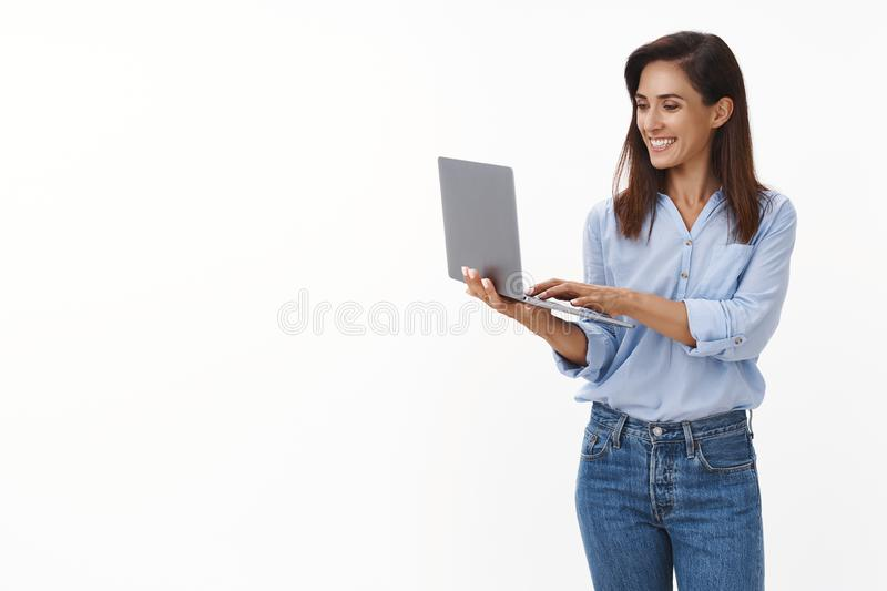 Lucky professional good-looking adult female entrepreneur writing text message coworker, smiling joyfully, hold laptop royalty free stock image