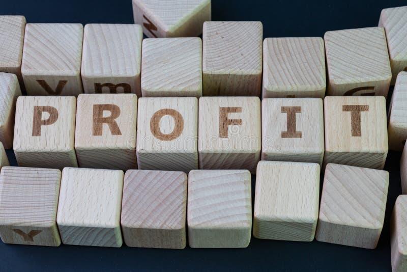 Lucro no invesment, no rendimento da empresa ou no conceito de renda financeira, bloco de madeira do cubo com liga do alfabeto o  fotos de stock