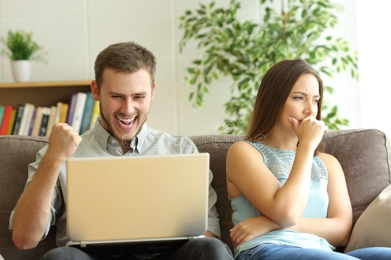 Luddite husband betting on line ignoring his sad wife. Luddite husband betting on line with a laptop ignoring his sad wife sitting on a couch at home royalty free stock photo