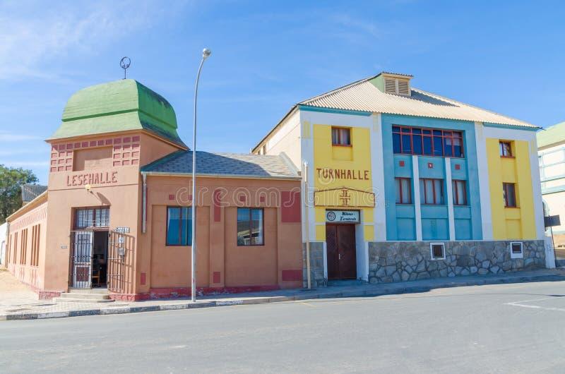 Luderitz, Namíbia - 8 de julho de 2014: Construções coloniais alemãs históricas de Turnhalle e de Lesehalle no dia ensolarado fotografia de stock royalty free