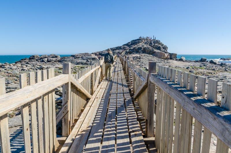 Luderitz, Namíbia - 9 de julho de 2014: Passagem de madeira que conduz ao ponto de Díaz em rochas no mar na península de Luderitz imagem de stock royalty free