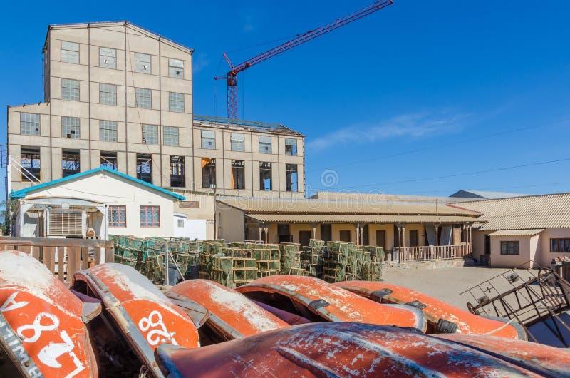 Luderitz, Namibia - 8 de julio de 2014: Barcos rojos y trampas de madera de la ostra y de los mariscos apiladas en el edificio co fotos de archivo