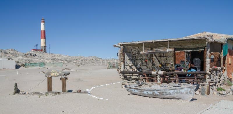 Luderitz, Namibia - 9 de julio de 2014: Café de Díaz y faro rojo y blanco en el punto de Díaz en la península de Luderitz foto de archivo