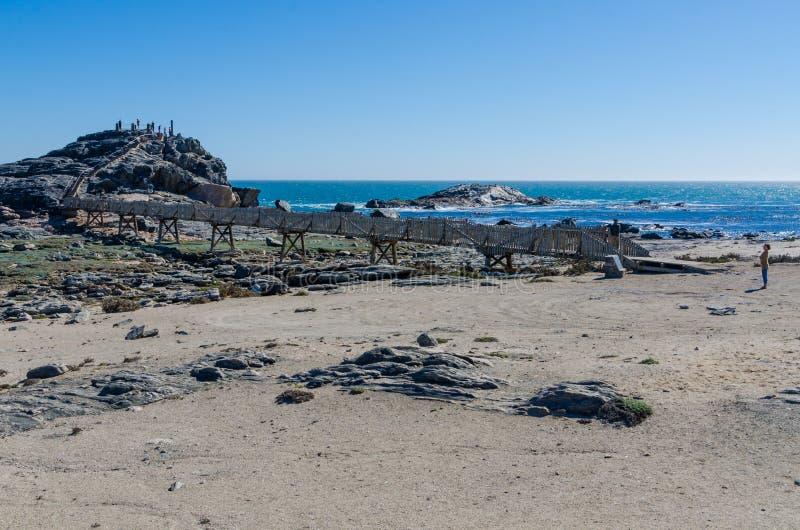 Luderitz, Namibia - 9 de julio de 2014: Calzada de madera que lleva al punto de Díaz en rocas en el mar en la península de Luderi imagenes de archivo