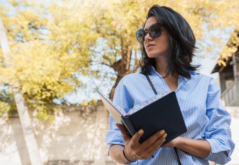 Ludzi, biznesu i pracy pojęcie, Rozochocony żeński enterpreneur używa notepad, workes plenerowi, planowanie jej dzień Potomstwa m obrazy stock