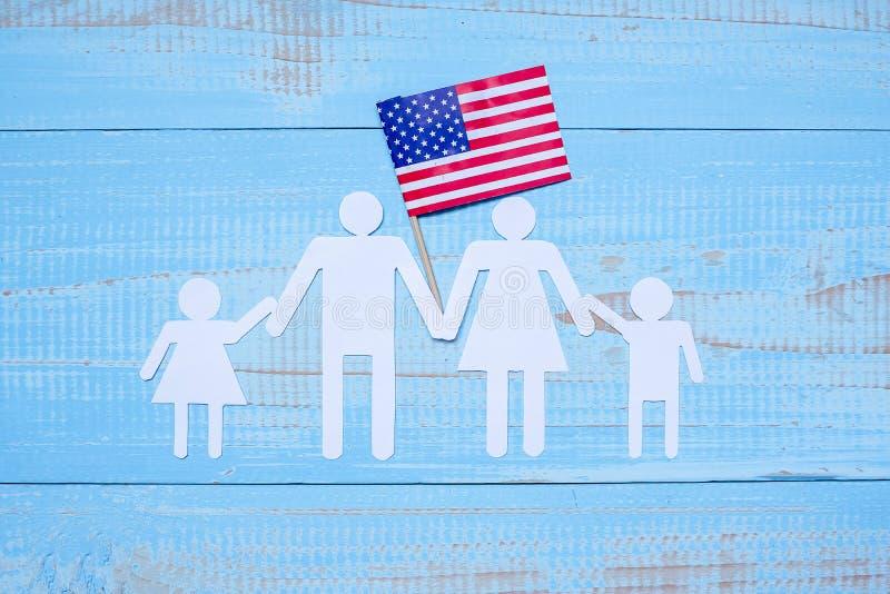 Ludzi lub rodziny papieru kształt z flagą Stany Zjednoczone Ameryka na błękitnym drewnianym tle USA wakacje weterani, zdjęcia royalty free