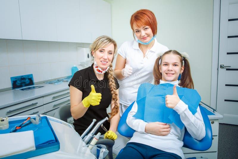 Ludzi, medycyny, stomatology i opieki zdrowotnej pojęcie, - szczęśliwy żeński dentysta sprawdza cierpliwych nastoletnich dziewczy zdjęcia royalty free