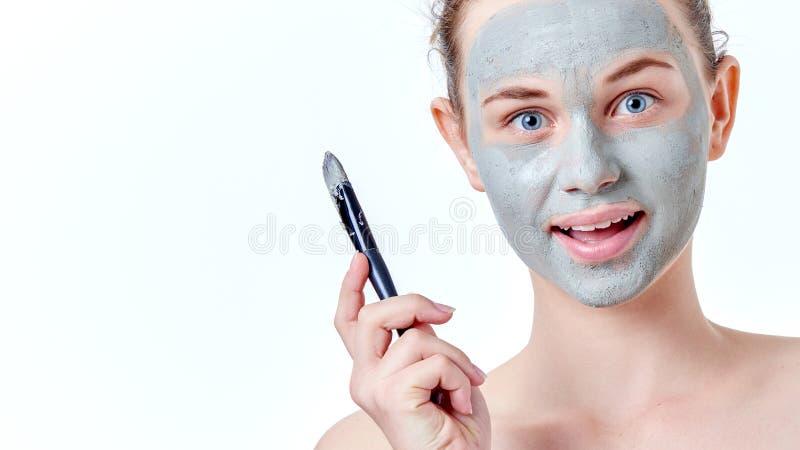 Ludzi, piękna, zdroju, kosmetologii i skincare pojęcie, Młoda nastoletnia dziewczyna stosuje twarzowego maskowego używa muśnięcie obrazy stock