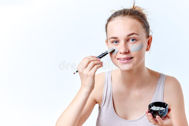 Ludzi, piękna, zdroju, kosmetologii i skincare pojęcie, Młoda nastoletnia dziewczyna stosuje twarzowego maskowego używa muśnięcie obraz royalty free