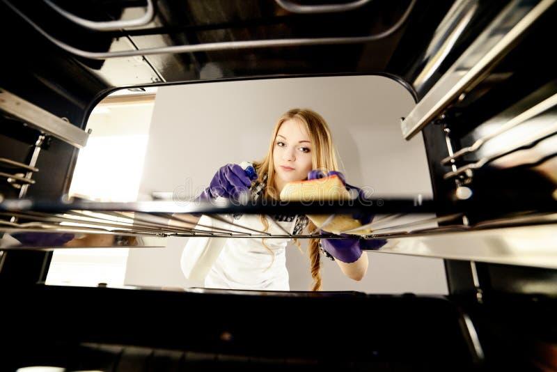 Ludzi, sprzątania i housekeeping pojęcie, - zamyka up kobiety ręka w ochronnej rękawiczce z gałganianą cleaning piekarnika kuchni obrazy stock