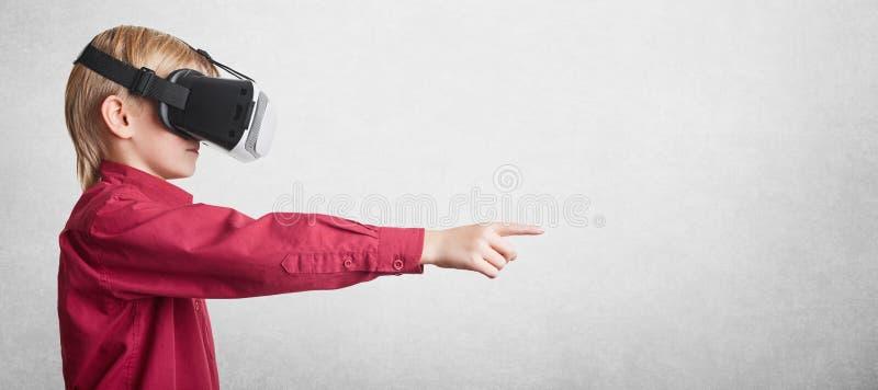 Ludzi, technologii i postępu pojęcie, Mała z podnieceniem chłopiec jest ubranym futurystycznych 3D szkła, doświadcza rzeczywistoś zdjęcia stock