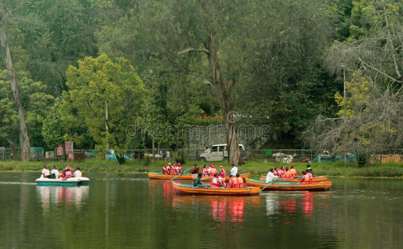 Ludzie łódkowatej jazdy przy kodaikanal jeziorem blisko łódkowatego domu obrazy stock