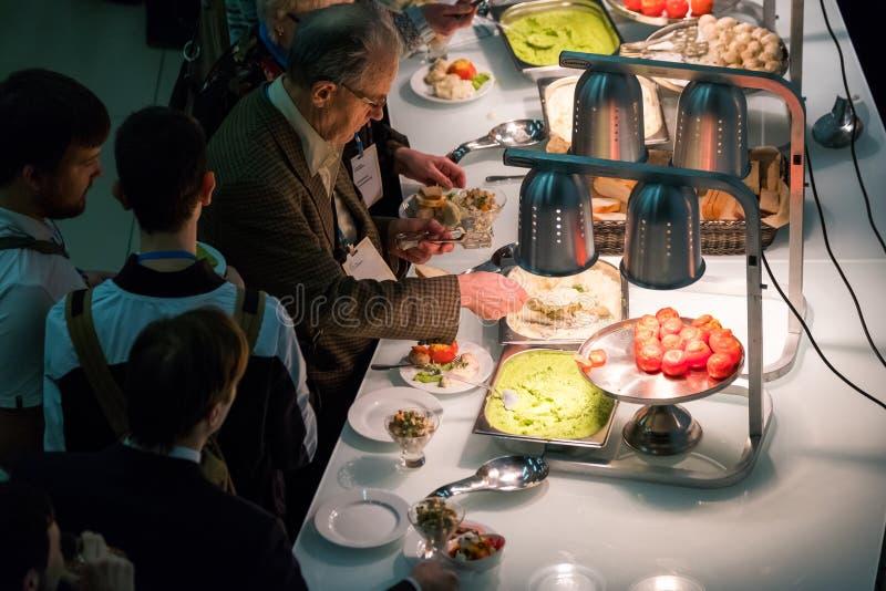 Ludzie biorą babeczki z rodzynkami na kawowej przerwie przy konferencją zdjęcie stock