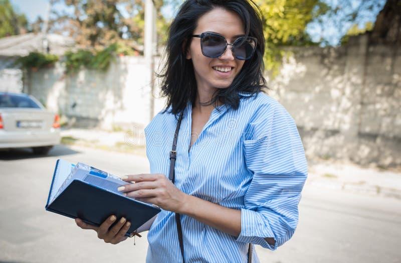 Ludzie, biznes, pracy pojęcie Uśmiechniętej rozochoconej brunetki biznesowy żeński kierownik używa notepad planować czas dla nowe zdjęcia royalty free