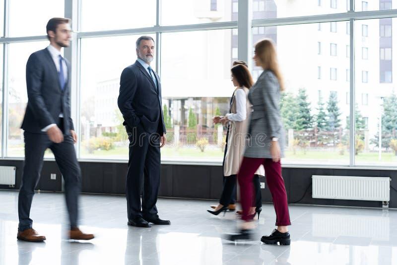 Ludzie biznesu śpieszy się w lobby tło plama zamazywał chwyta frisbee doskakiwania ruch obrazy stock