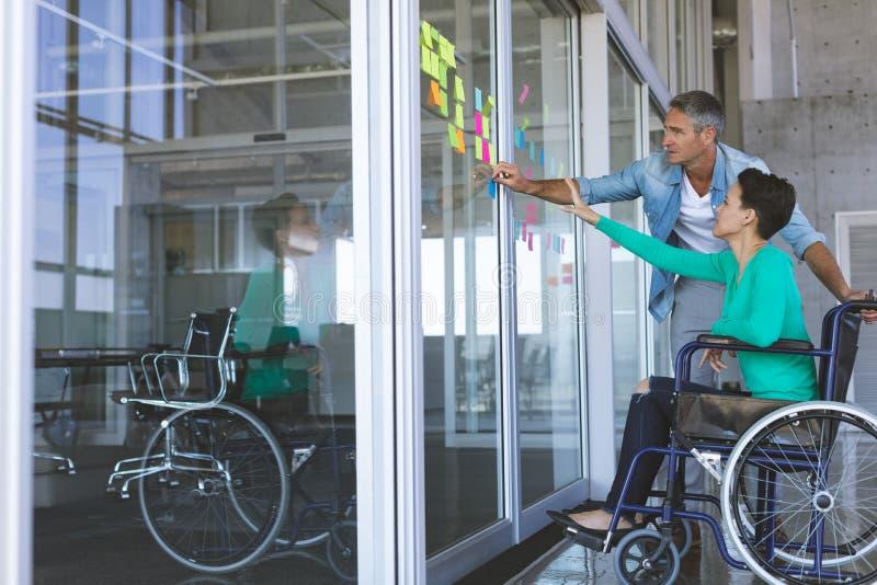 Ludzie biznesu dyskutuje nad kleistymi notatkami na szklanej ścianie w biurze zdjęcia royalty free