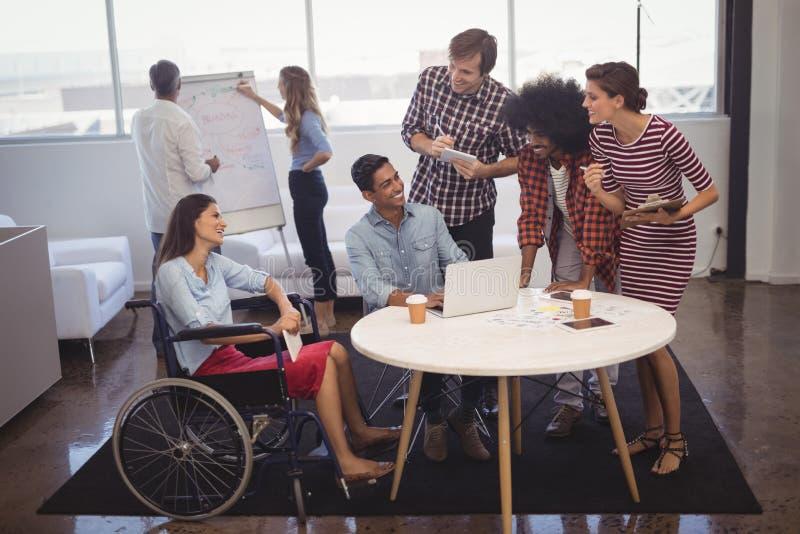 Ludzie biznesu dyskutuje strategie z niepełnosprawnymi kolegami w kreatywnie biurze fotografia stock