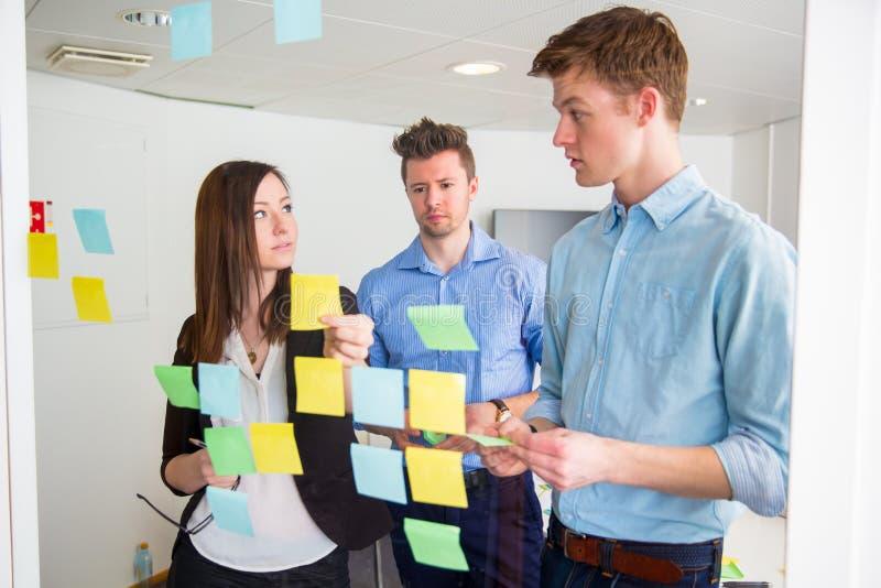 Ludzie Biznesu Komunikuje Podczas gdy Wtykający notatki Na szkle zdjęcia stock