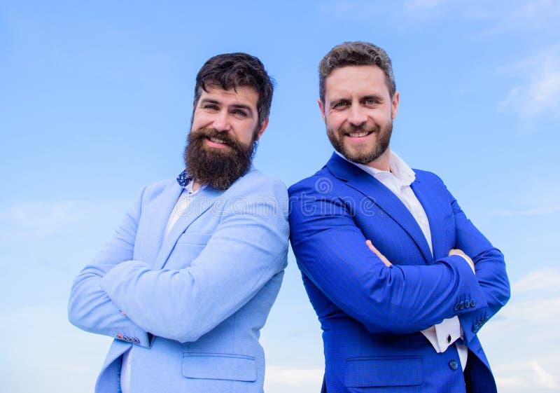 Ludzie biznesu pojęć Brodaci ludzie biznesu pozuje pewnie Biznesowych mężczyzn niebieskiego nieba statywowy tło Doskonalić wewnąt fotografia royalty free