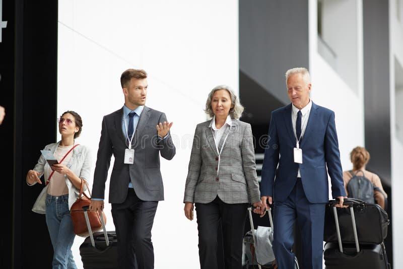 Ludzie biznesu rusza się wzdłuż lotniska z walizkami obraz royalty free