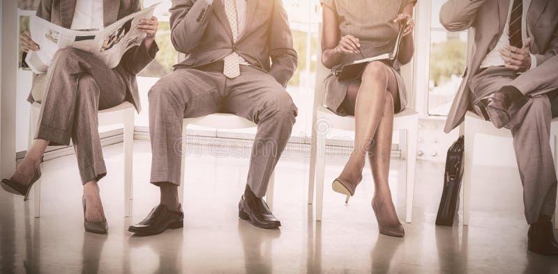 Ludzie biznesu siedzi na krzesłach obrazy stock
