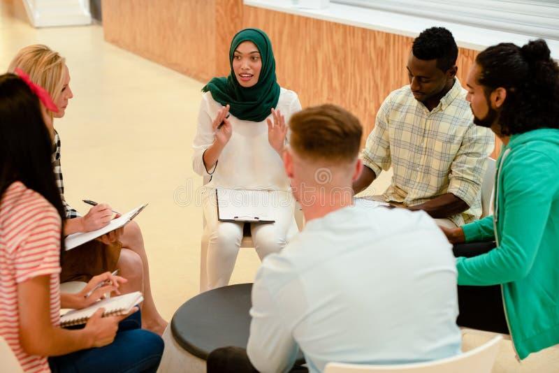 Ludzie biznesu siedzi wpólnie i ma grupową dyskusję w nowożytnym biurze zdjęcie stock