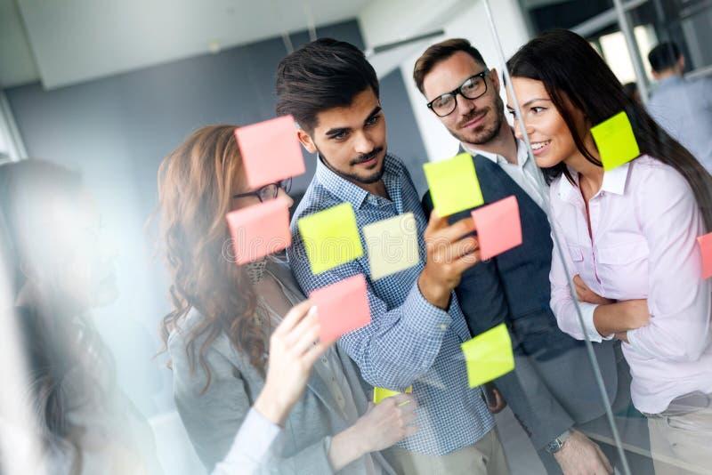 Ludzie biznesu spotyka przy biurem i use poczta ono zauważa dzielić pomysł obraz stock