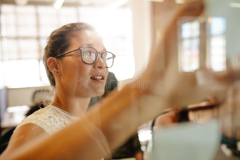 Ludzie biznesu spotyka w biurze dyskutuje nad kleistymi notatkami obraz royalty free