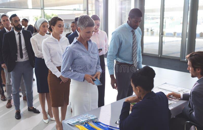 Ludzie biznesu sprawdza wewnątrz przy konferencyjnym rejestracja stołem fotografia royalty free