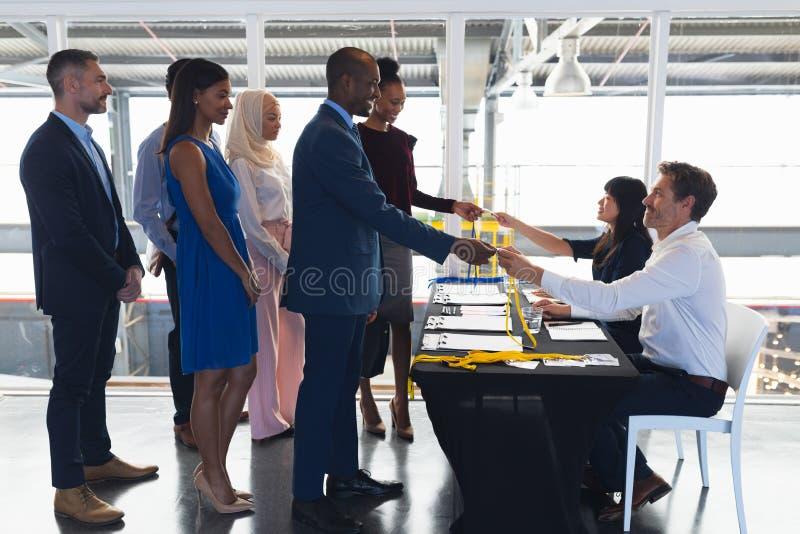 Ludzie biznesu sprawdza wewn?trz przy konferencyjnym rejestracja sto?em zdjęcia stock