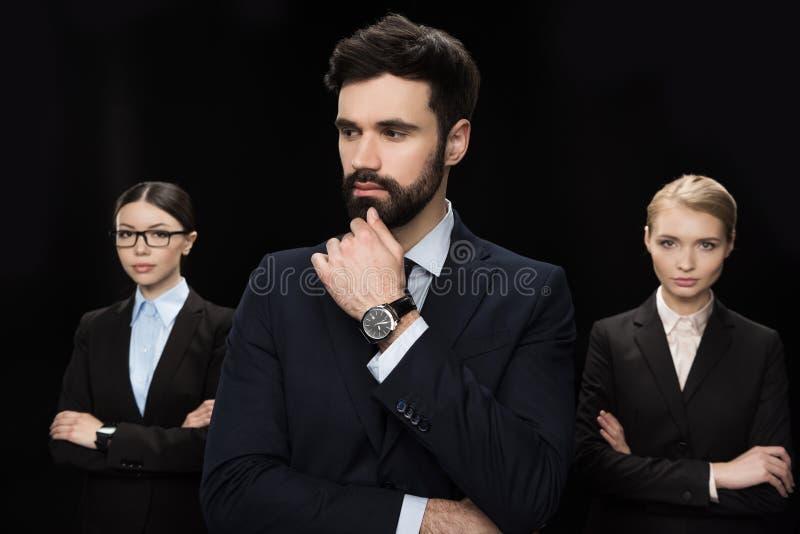 Ludzie biznesu stoi z krzyżować rękami odizolowywać na czarnego, biznesowego założenia pojęciu, obrazy stock