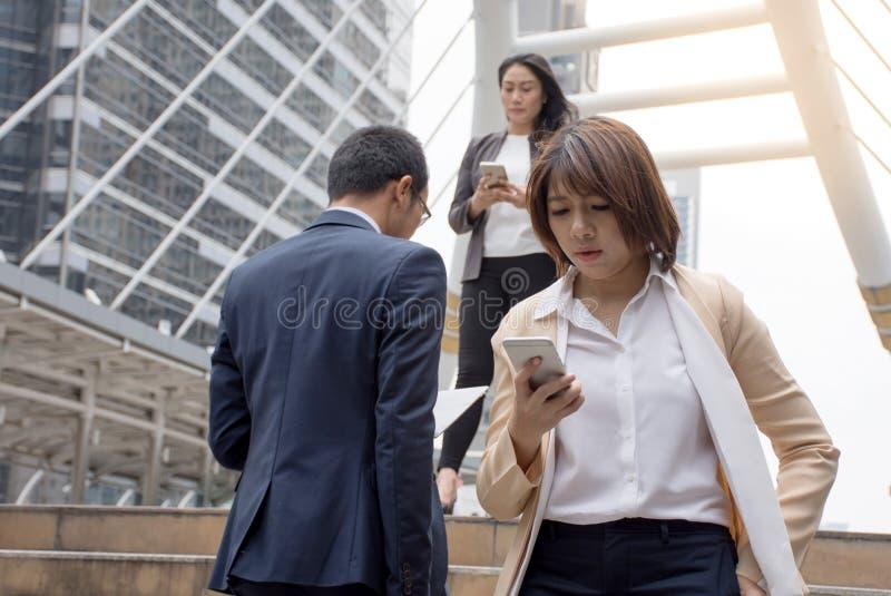Ludzie biznesu trzyma telefon komórkowego i odprowadzenie na nowożytnym przejściu fotografia stock