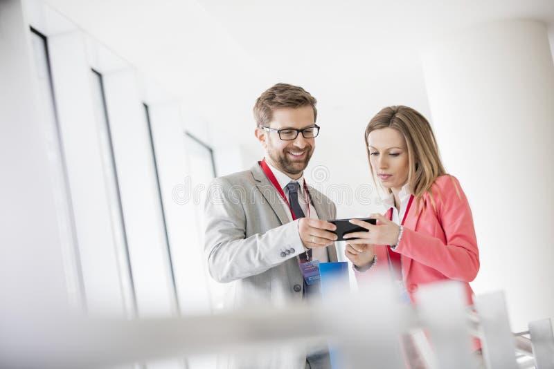 Ludzie biznesu używa mądrze telefon w convention center obraz royalty free