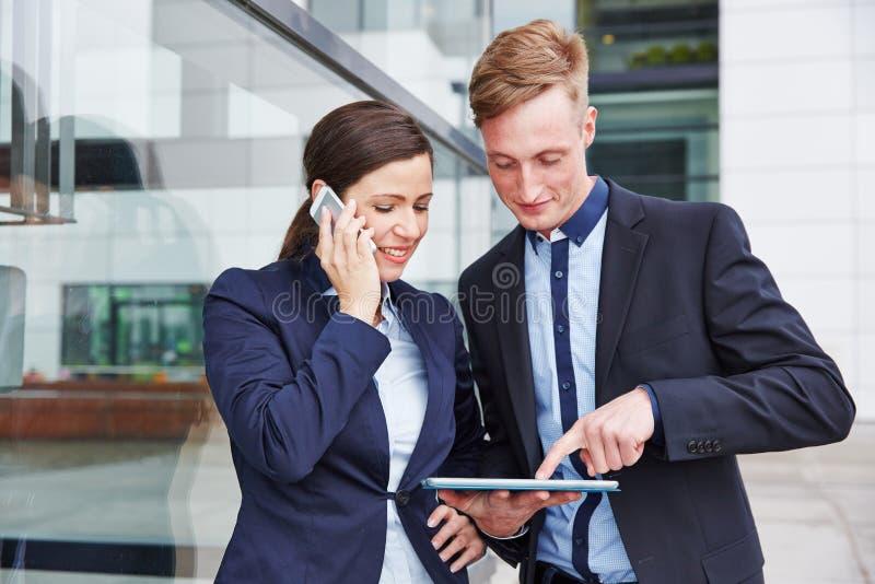Ludzie biznesu używa smartphone i pastylki komputer zdjęcia stock