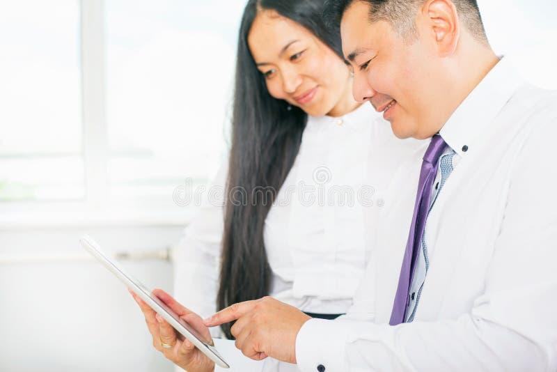 Ludzie biznesu ubierali w białym używa pastylka komputerze osobistym przy biurem obraz stock