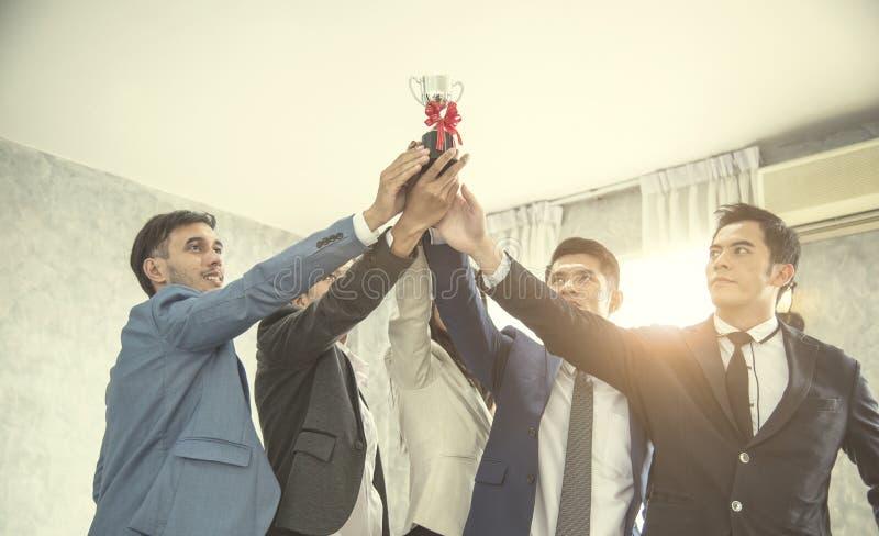 Ludzie biznesu z trofeum zwycięstwo pojęcie praca zespołowa i uni obrazy royalty free