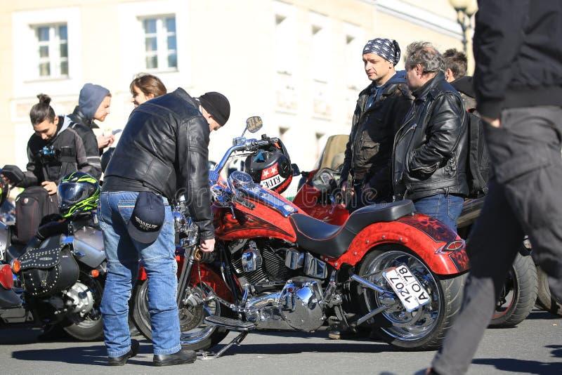 Ludzie blisko czerwonego obyczajowego motocyklu Harley-Davidson na słonecznym dniu obraz stock