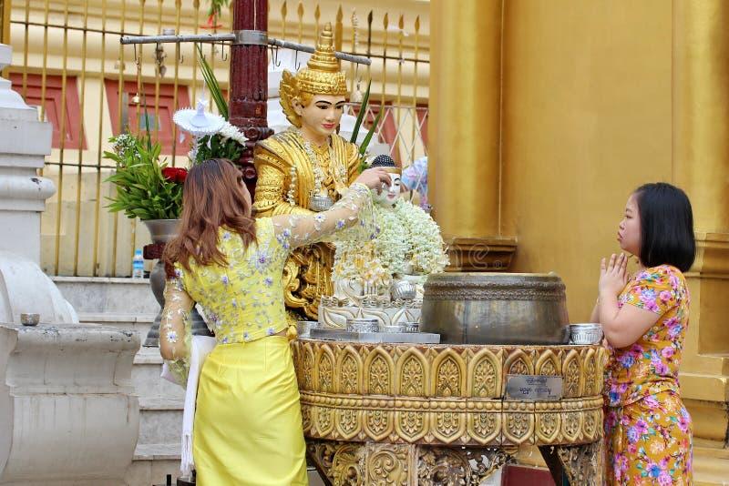 Ludzie buddyjskich dewotek kąpać się dla błogosławieństw myją Buddha statuę przy Shwedagon pagodą 1 5 świętych miejsc zdjęcia stock