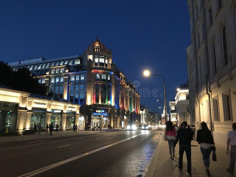 Ludzie chodzą w wieczór lata ulicach Moskwa Iluminujący budynek sklep «Detsky mir fotografia stock