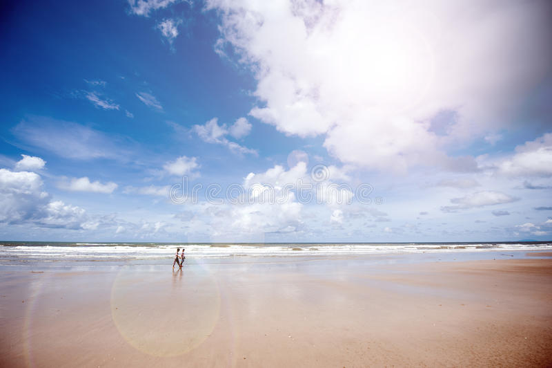 Ludzie chodzą wzdłuż pustej plaży z błękita jasnego niebem w lecie zdjęcia royalty free