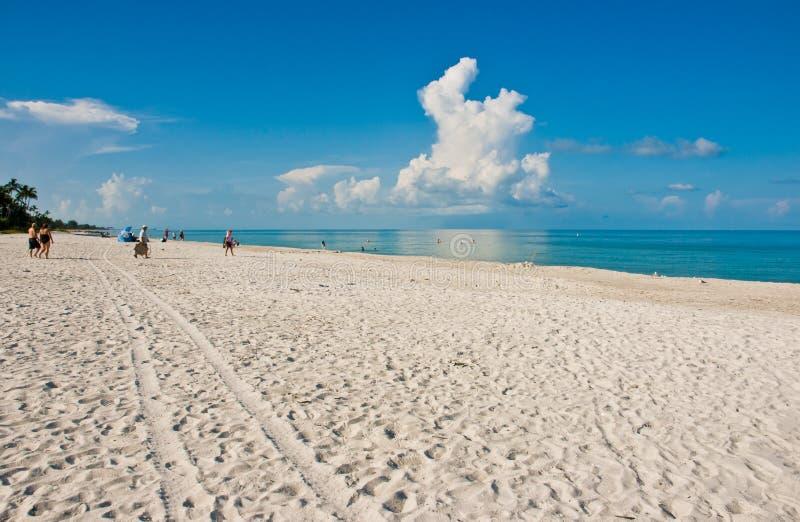 Ludzie chodzi na białej, piaskowatej plaży, tropikalna linia brzegowa zdjęcia stock