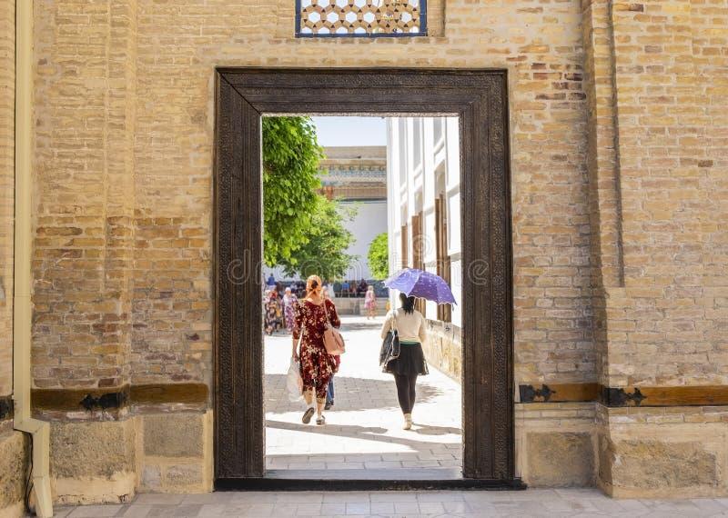 Ludzie chodzi przez drzwi w pamiątkowym kompleksie Khoja Bahauddin Nakshband, Bukhara, Uzbekistan obraz stock